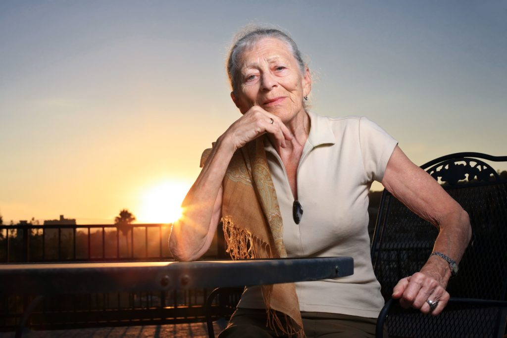 Senior woman sitting at the table outdoors at sunset.